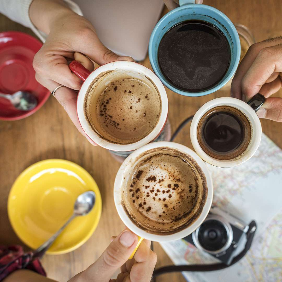 An image of several people toasting their cups of coffee