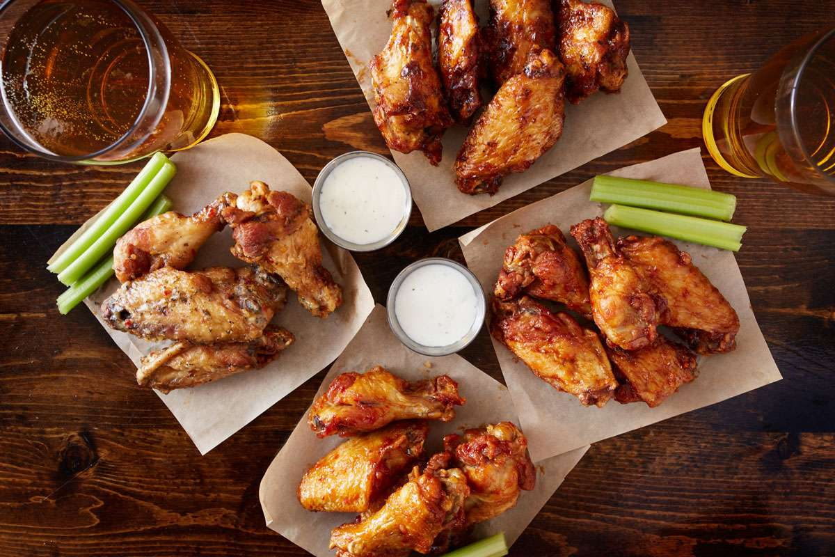 Four plates of chicken wings