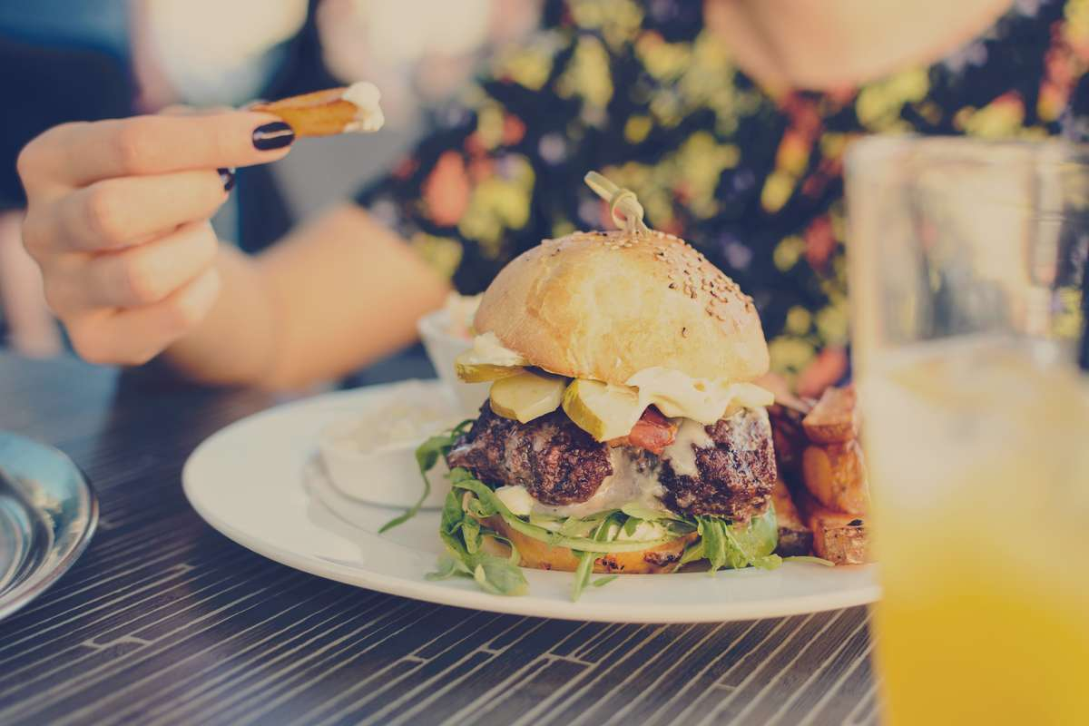person holding french fry over burger