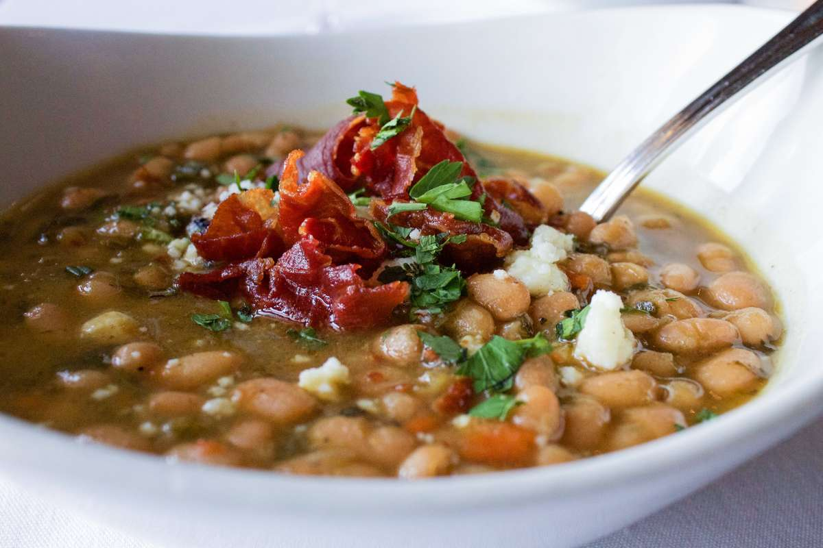 Close up of bean soup with a spoon in it