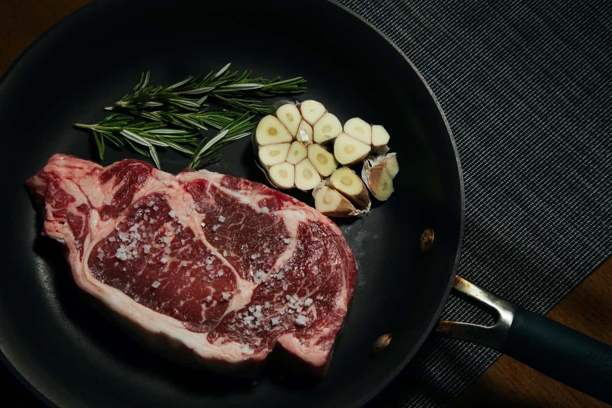Raw steak with garlic and rosemary