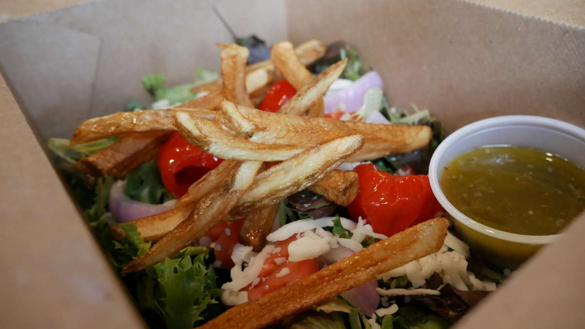 Salad with fries on top and a side of dressing