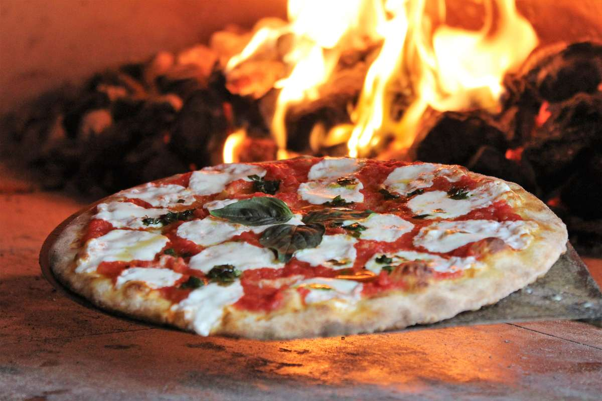Pizza coming out of brick oven