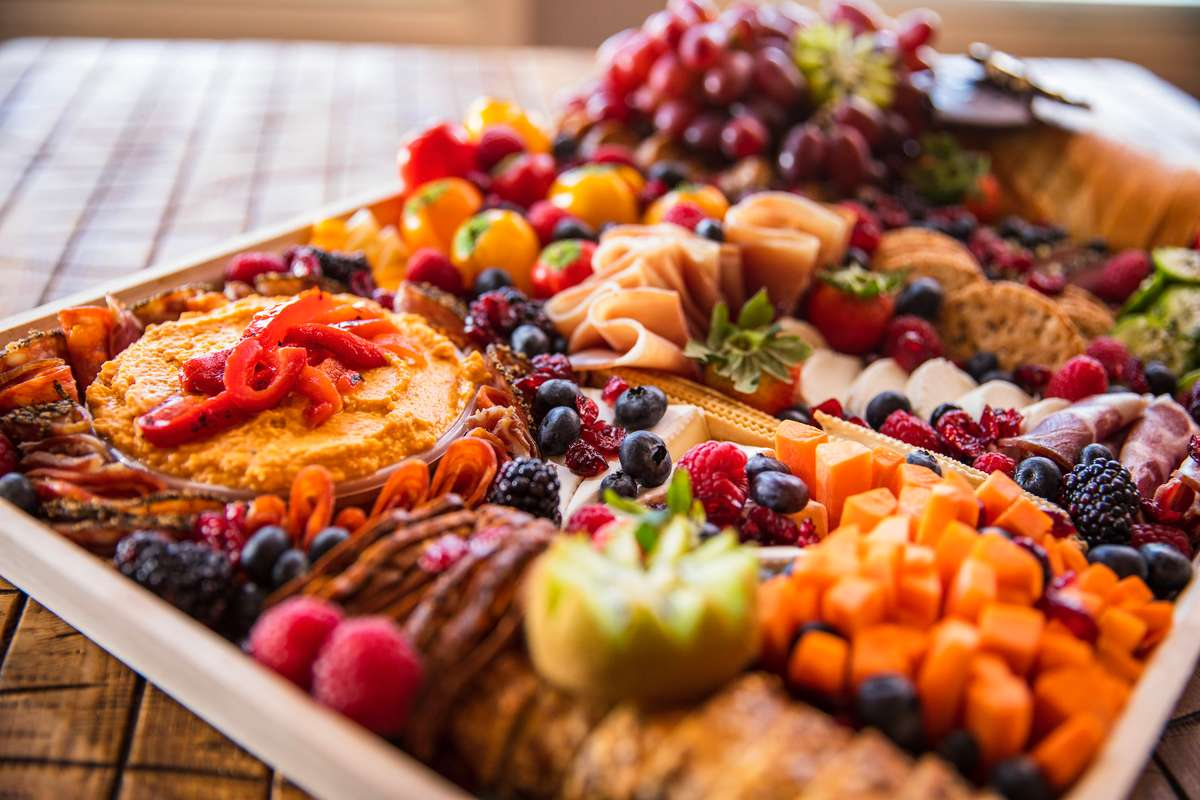 Charcuterie board with various vegetables and fruit spreads