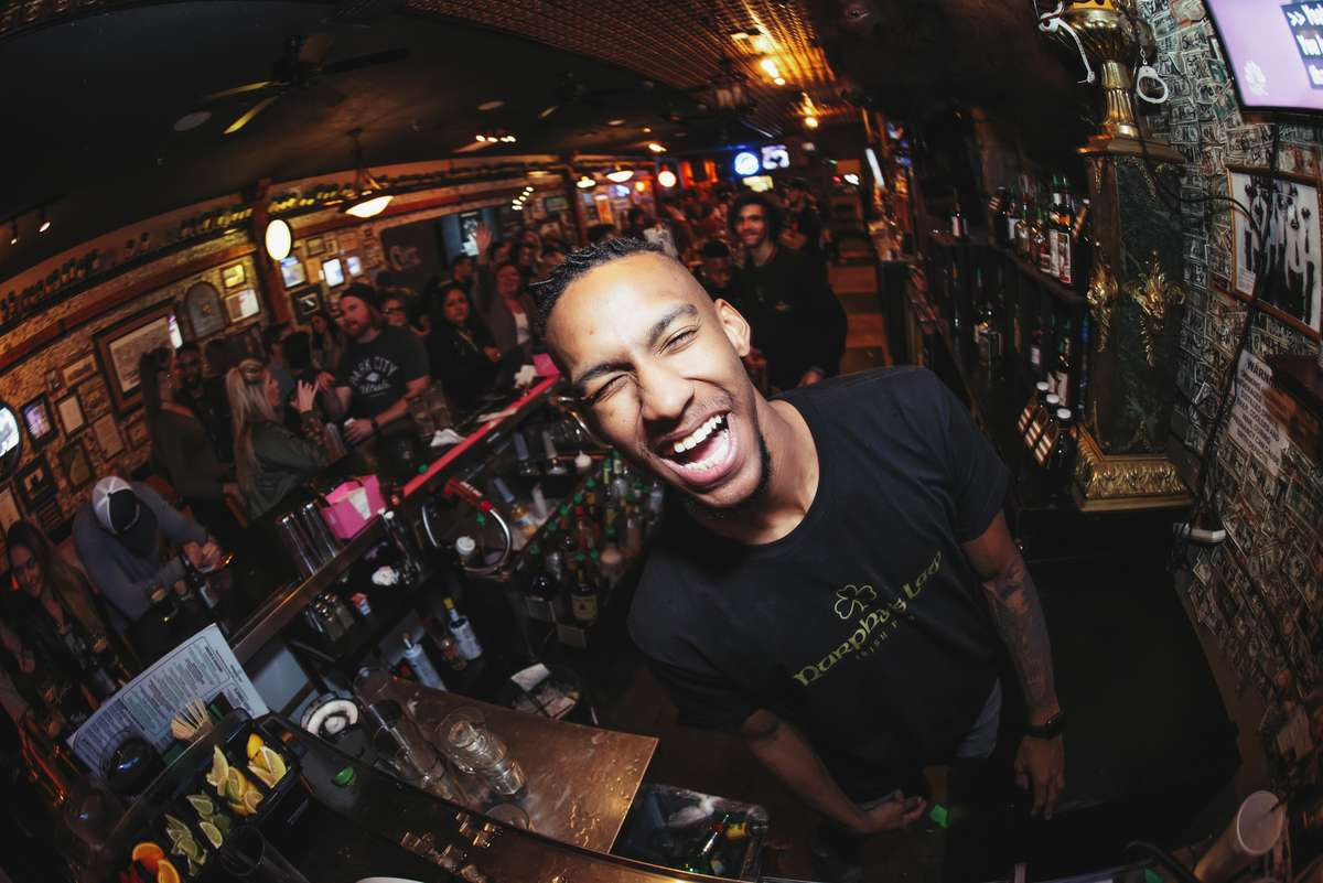 Waiter laughing for the camera in front of a crowded bar