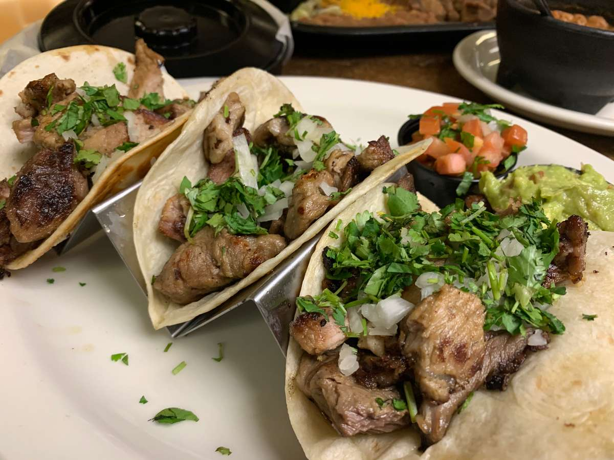 three tacos on wooden board with three peppers