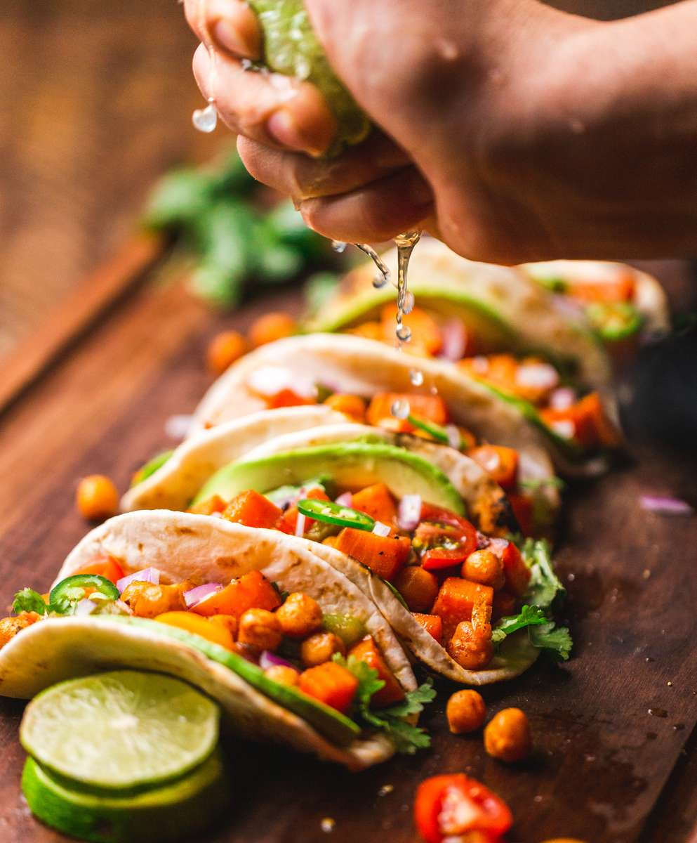 hand squeezing a lime over four tacos