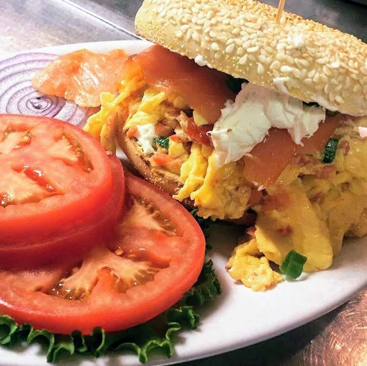 Lox, egg and onion scramble open face on a toasted bagel smothered with lox