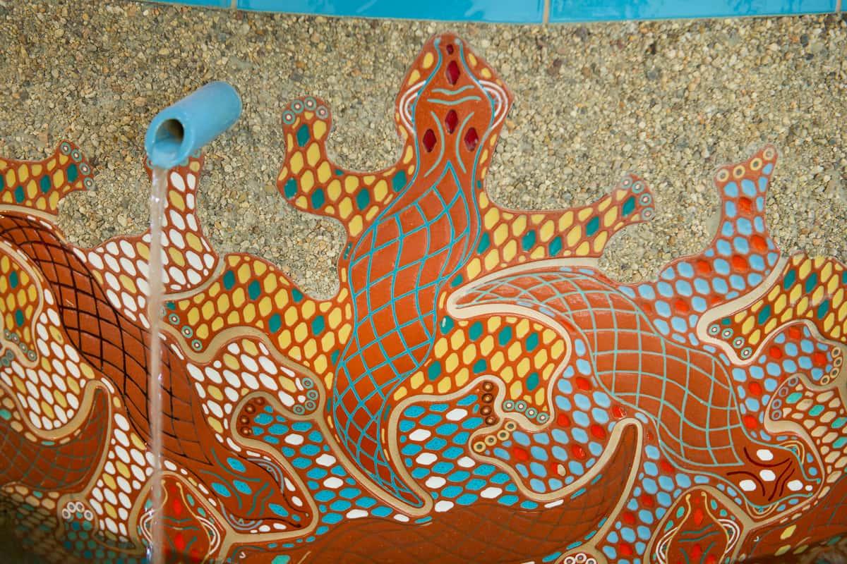 Closeup of terra cotta gecko design on Urth fountain