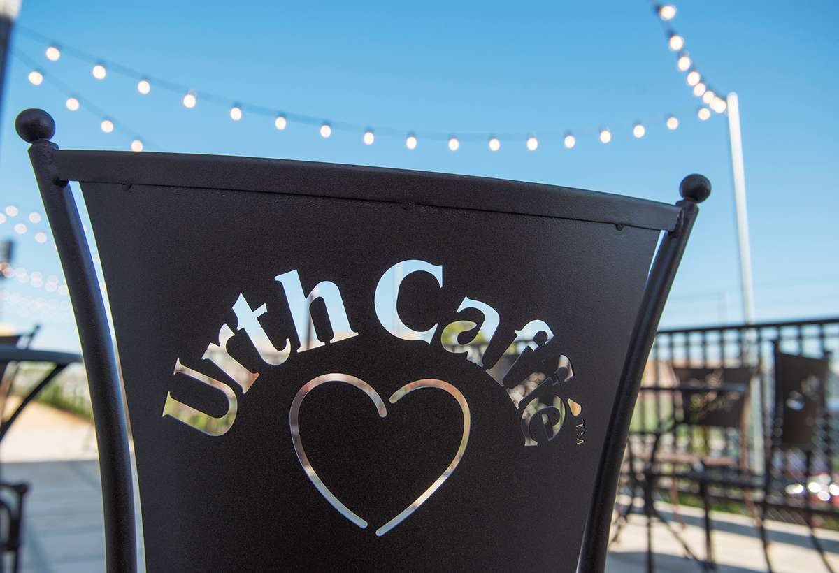 Back of an Urth Caffe metal chair silhouetted against blue sky