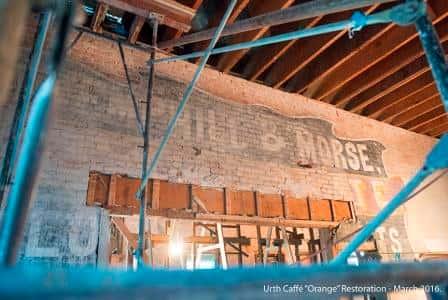 Hemphill & Morse advertising mural is revealed on interior brick wall