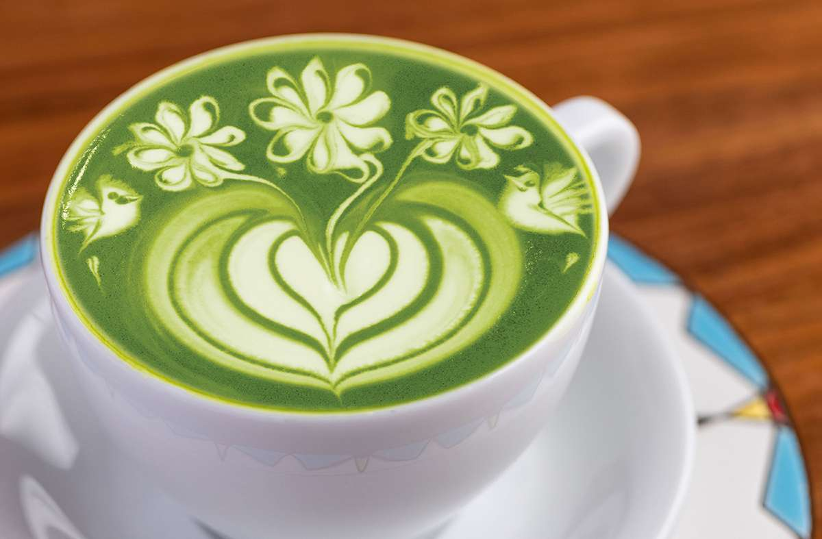 flowers are etched into a tea latte's foam