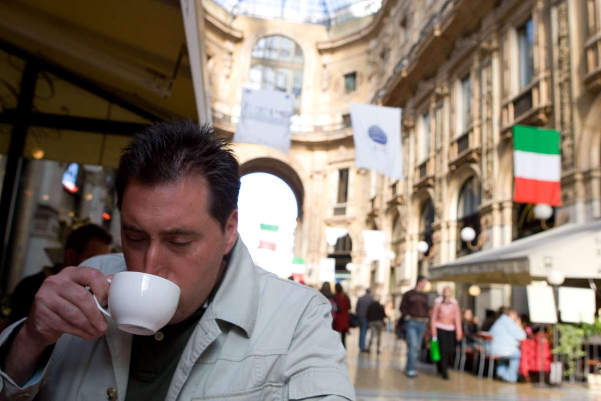 Man sips caffe latte outside a cafe in Venice Italy.
