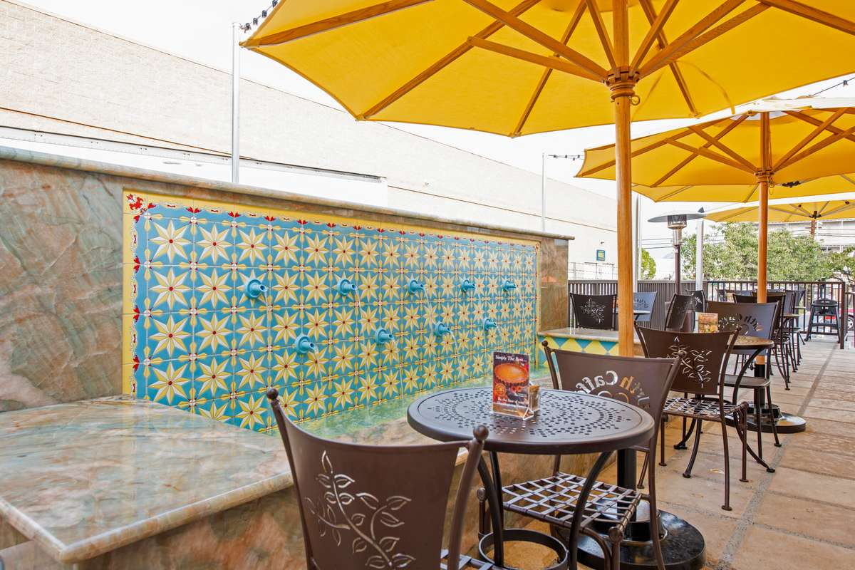 Patio tables with open bright yellow umbrellas and tile fountain