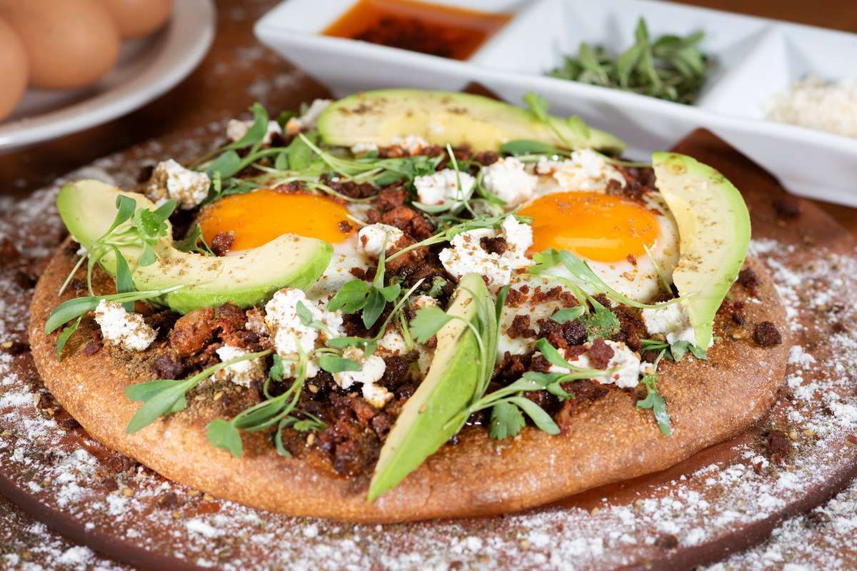 Pizza Huevos Rancheros with eggs, beans, and soy chorizo topped with almond cheese, ripe avocado and micro cilantro on pizza crust