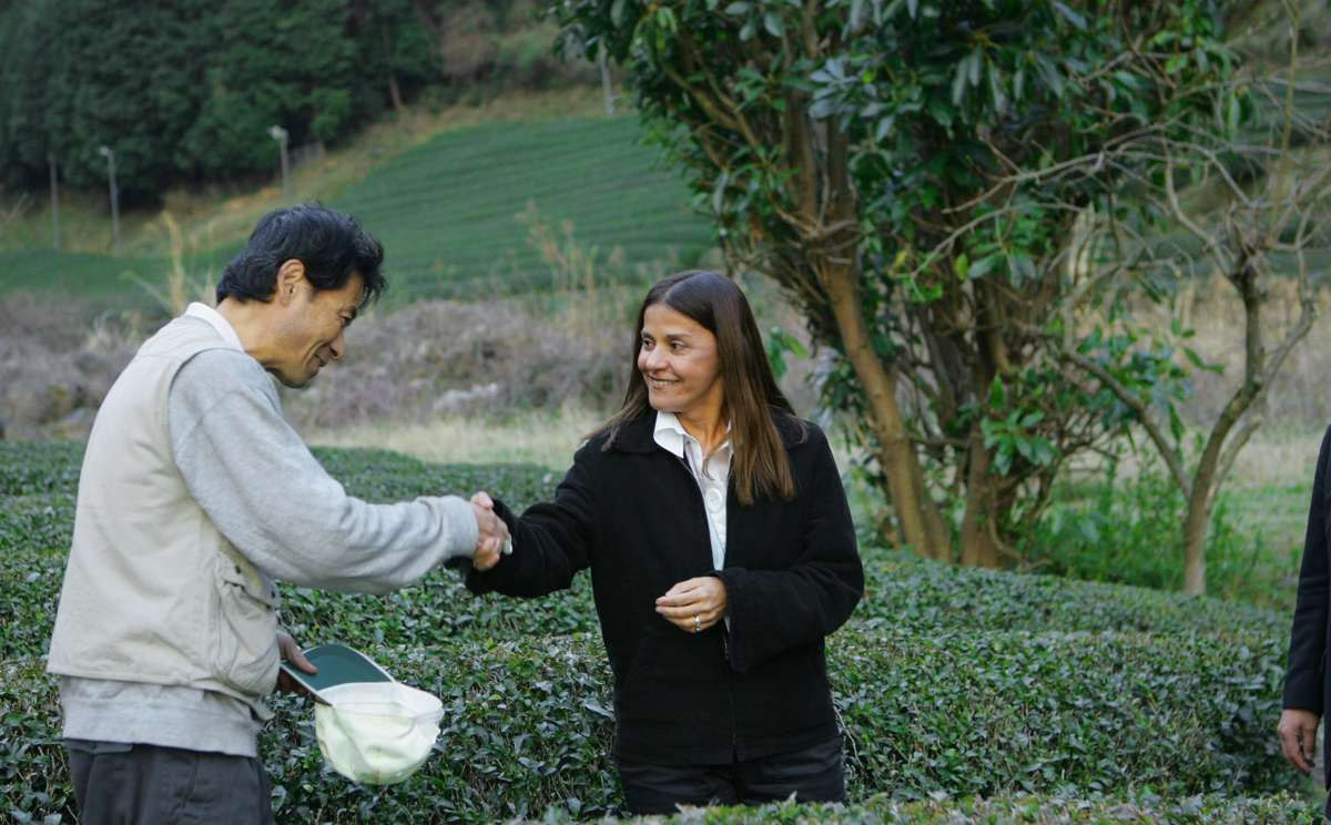Jilla Berkman shaking hands with tea farmer Akihiro Nakai.