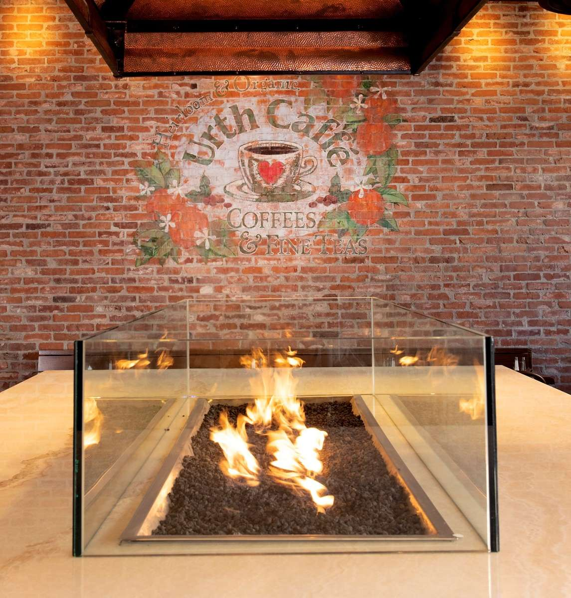 Interior gas fire pit at the center of white marble table. Faded Urth Orange logo is on brick wall in the back.