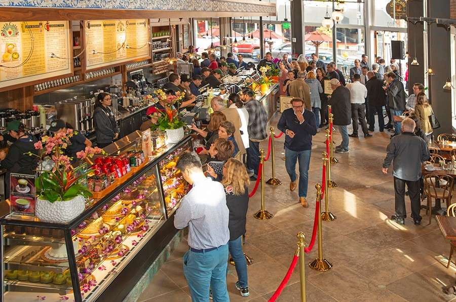 Inside view of guests waiting in line and looking into pastry display cases.