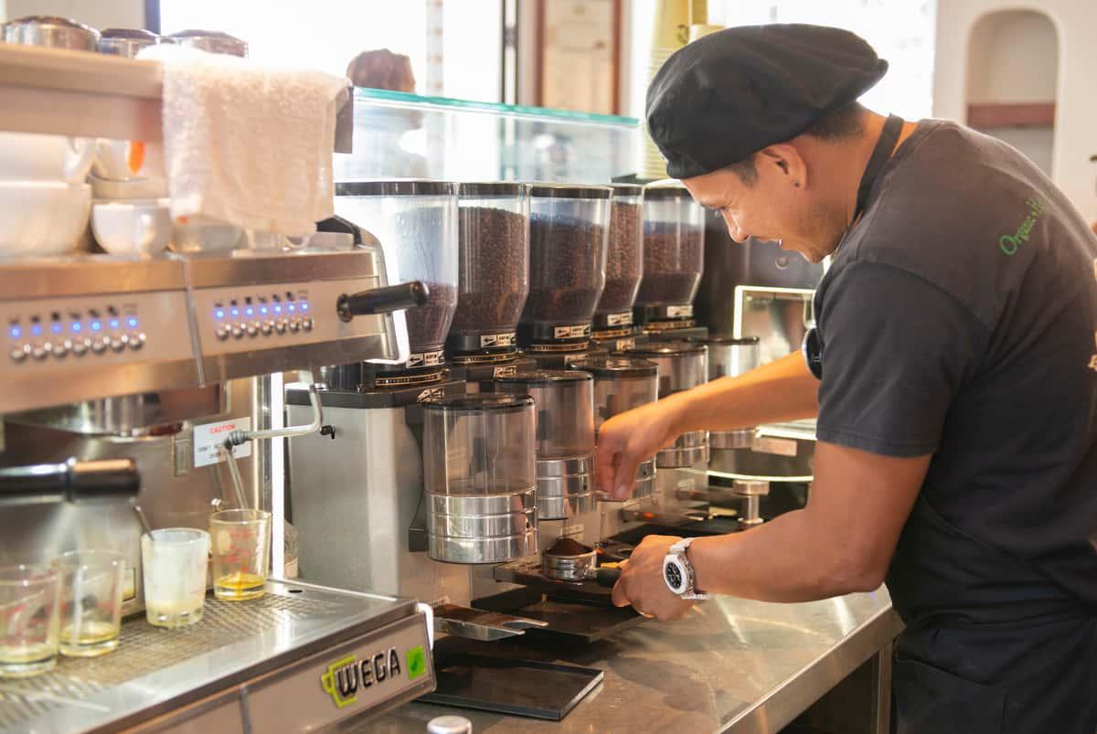 Barista measures espresso beans for a latte