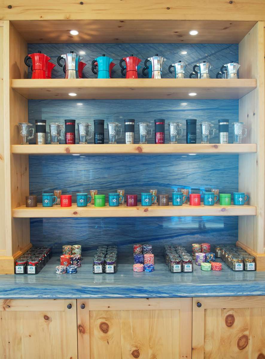 Shelves with travel mugs, tea canisters and glass cups