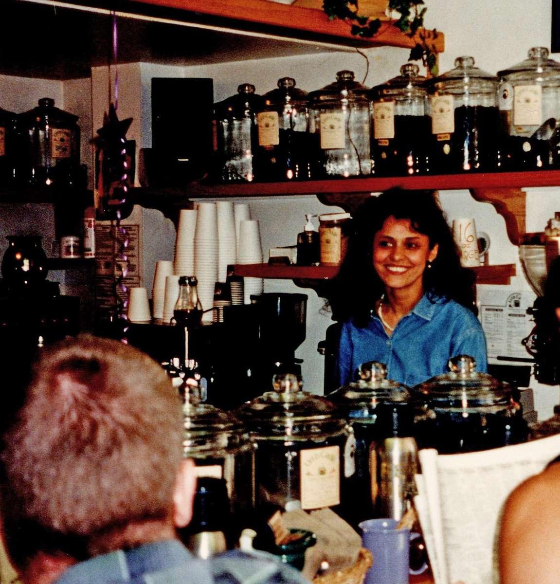 Jilla Berkman stands behind counter at cafe