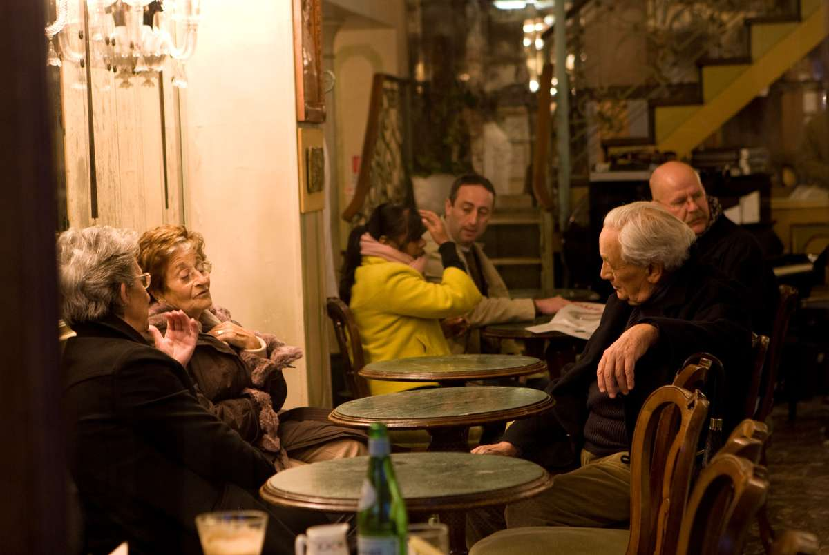 People chat around tables outside a Venice, Italy cafe.