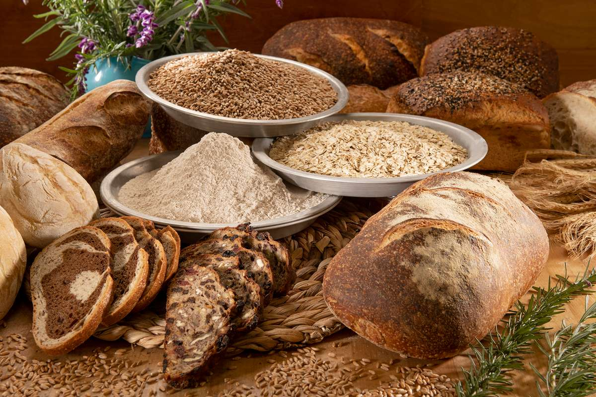 Loaves of bread and bowls of whole grains, flours