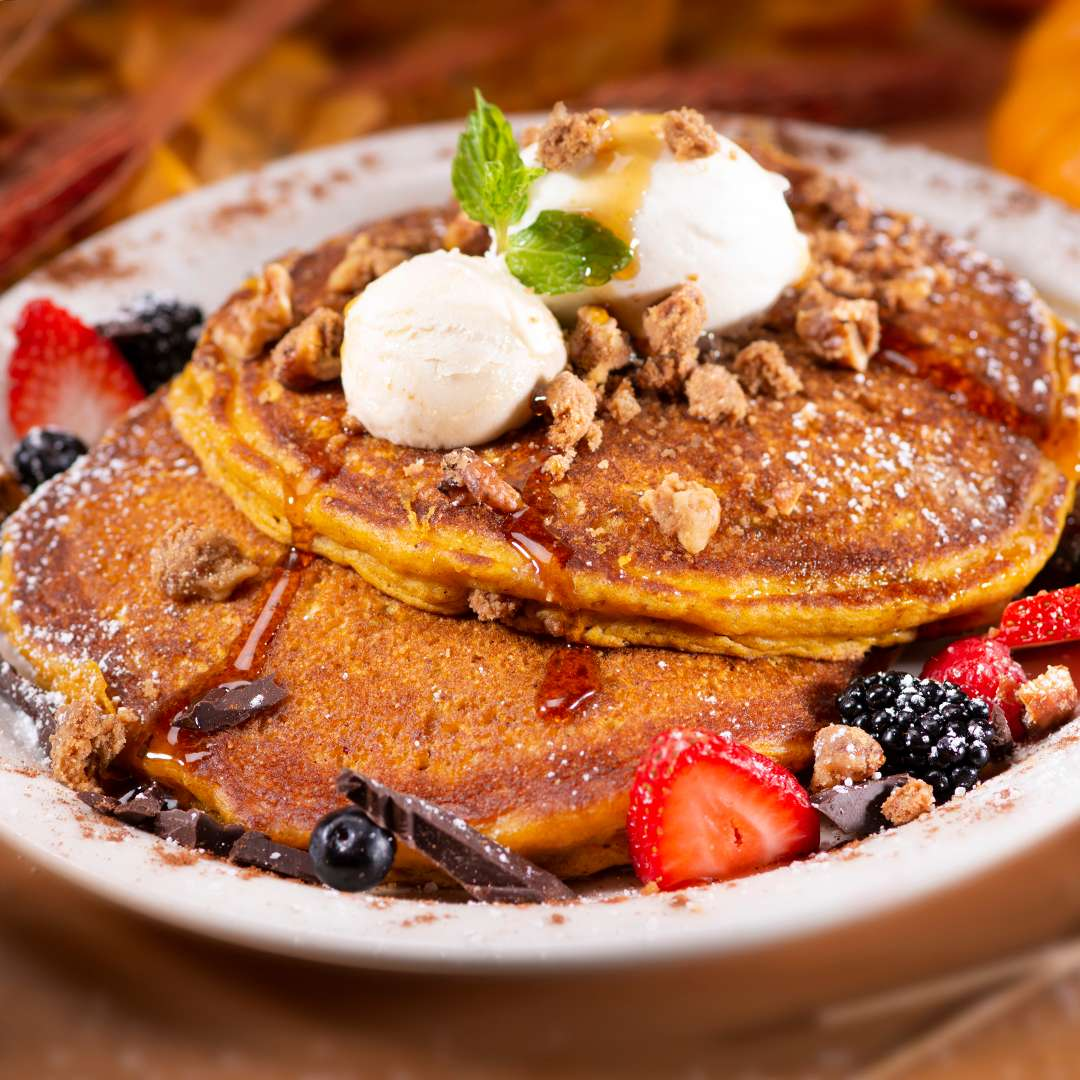 Two Pumpkin Pancakes topped with dollops of whipped cream, Acacia honey butter and pie crust crumbles, garnished with fresh berries
