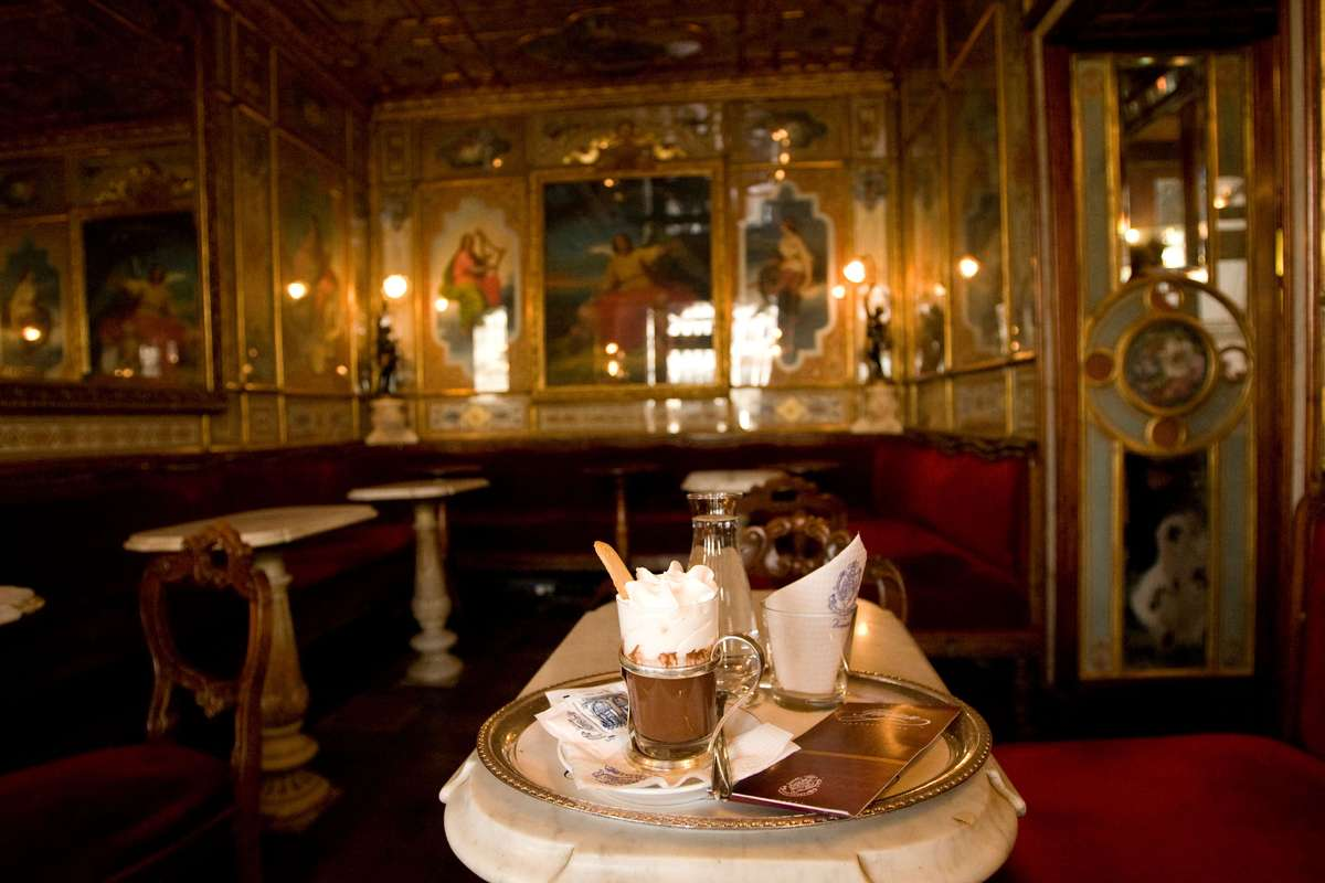 Platter of coffee and desserts inside a golden accented interior of a cafe in Venice Italy