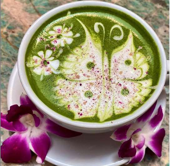 Green Rose Latte with detailed butterfly design made with green tea, oat milk, with rose petal bits sprinkled on top