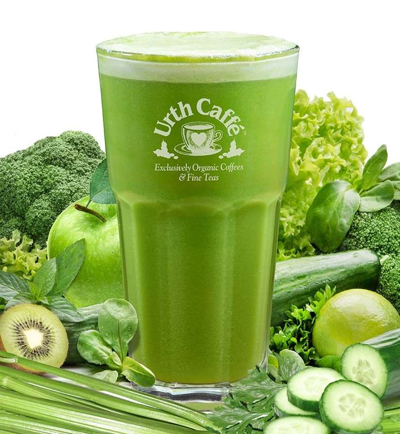 Glass of green juice with a variety of green fruits and vegetables in background