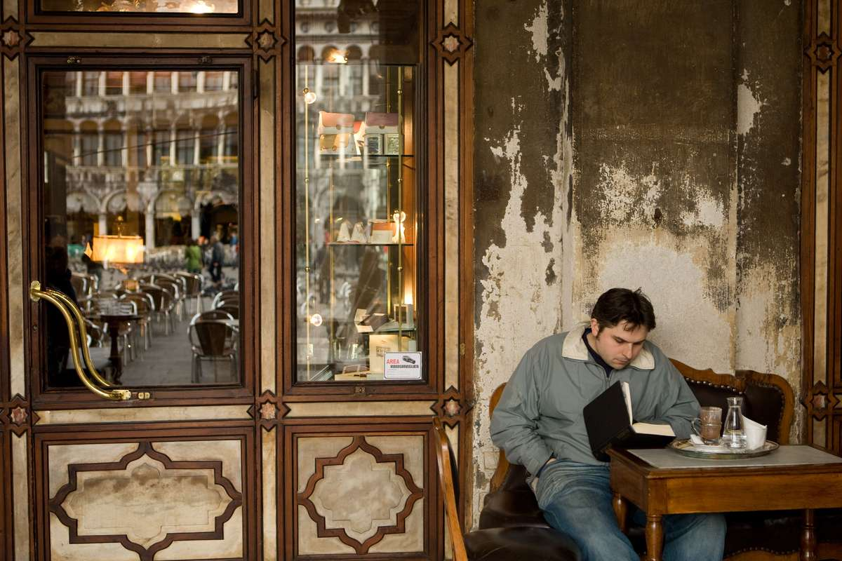 man reading a book at a table outside of an Italian cafe