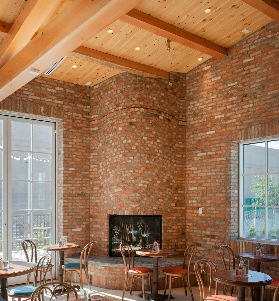 Rounded fireplace of reclaimed brick in corner of room with high ceilings and large windows.