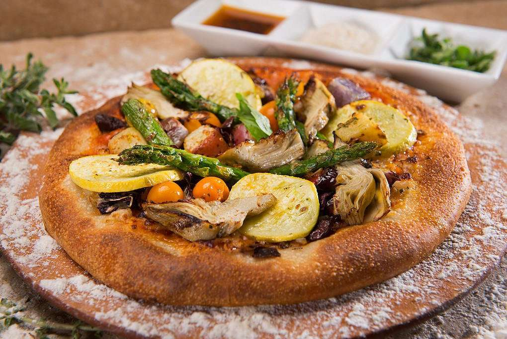 Left photo - Pizza Primavera topped with fresh vegetables.