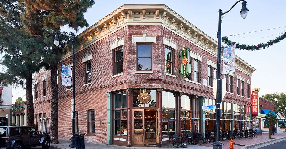 View of corner with restored two story brick building of Urth Caffe Orange