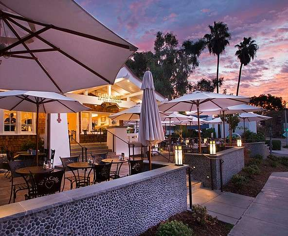 Sunset view of Urth Caffe Laguna Beach front porch and patio with tables and umbrellas