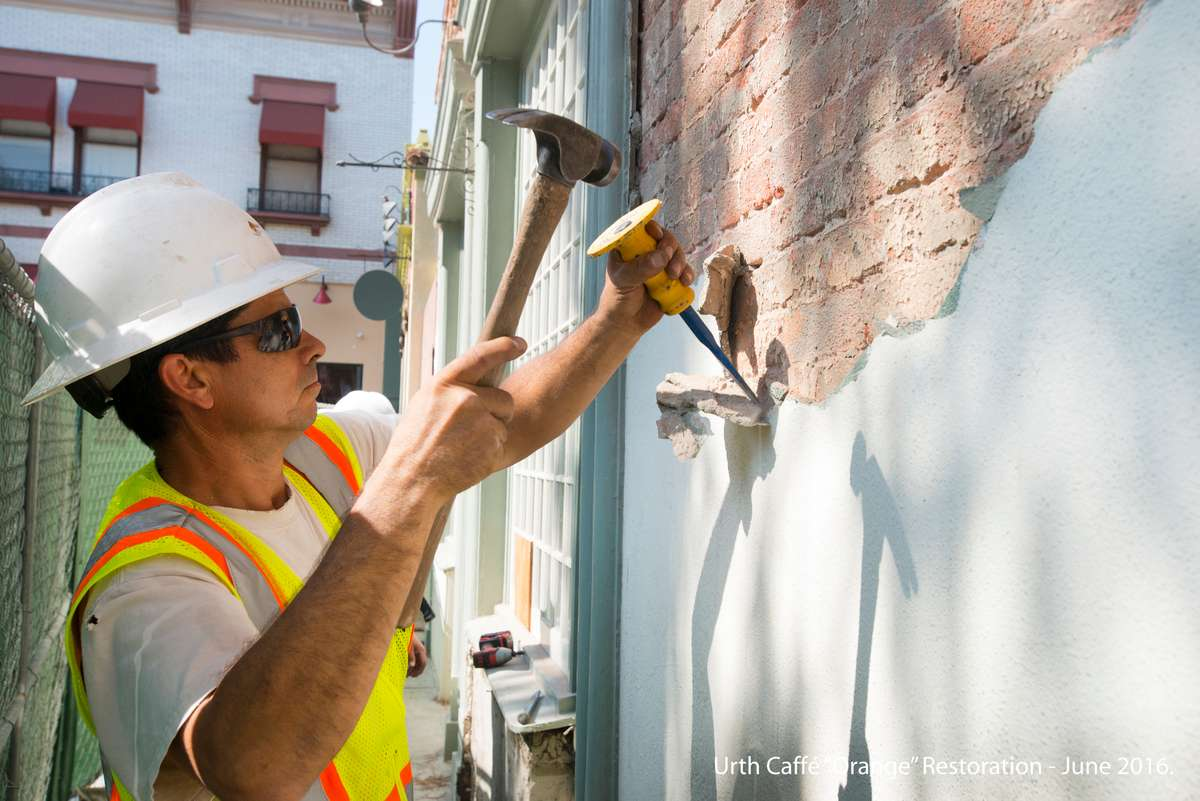 Construction worker uses hammer and chisel to peel layers of white plaster off brick wall