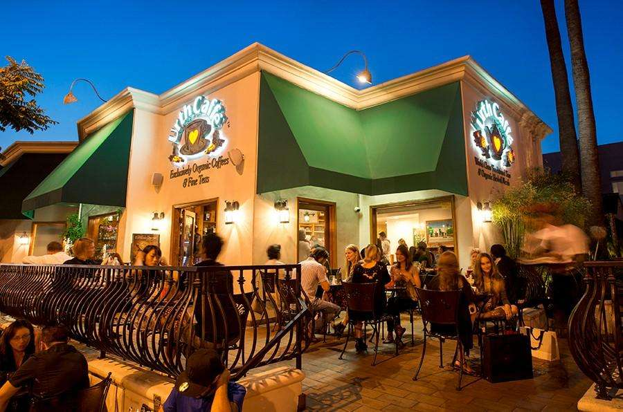 Exterior view of Urth Caffe Melrose with guests sitting at tables on patio