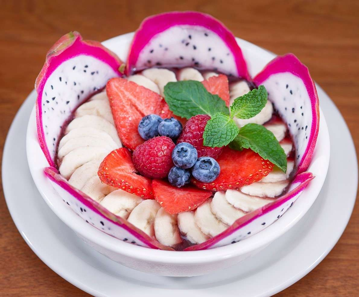 Urth Acai Bowl in white bowl with sliced fruits - acai, bananas, strawberries, garnished with blueberries and raspberries and mint sprig