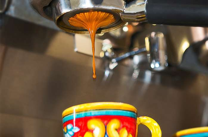 Espresso coffee drips into a colorful cup