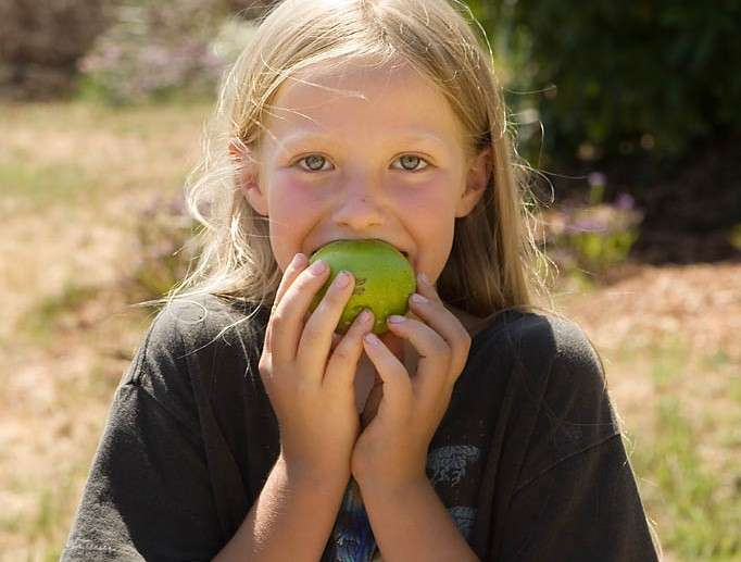 Young girl take a bite out of a green apple