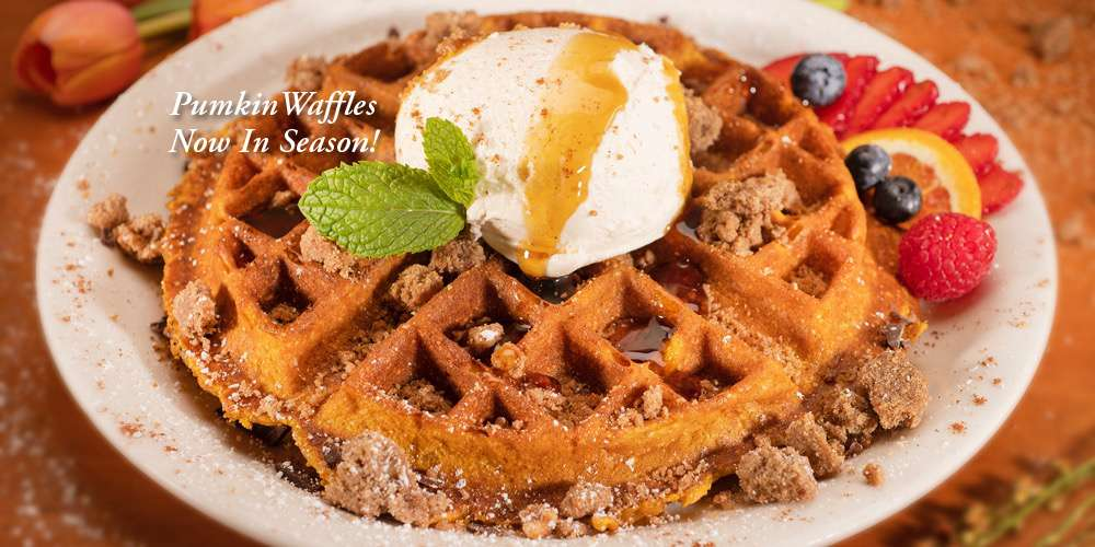 Urth pumpkin waffle topped with a scope of vanilla ice cream and brown sugar crumbles with sliced strawberries on a white plate.