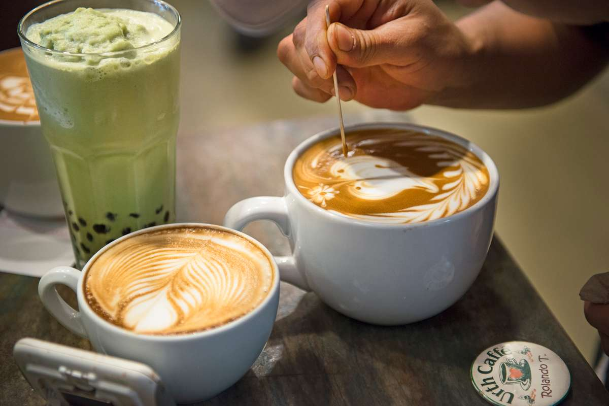 Three drinks, a blended ice matcha boba, a latte and another latte with barista etching a butterfly design into the foam