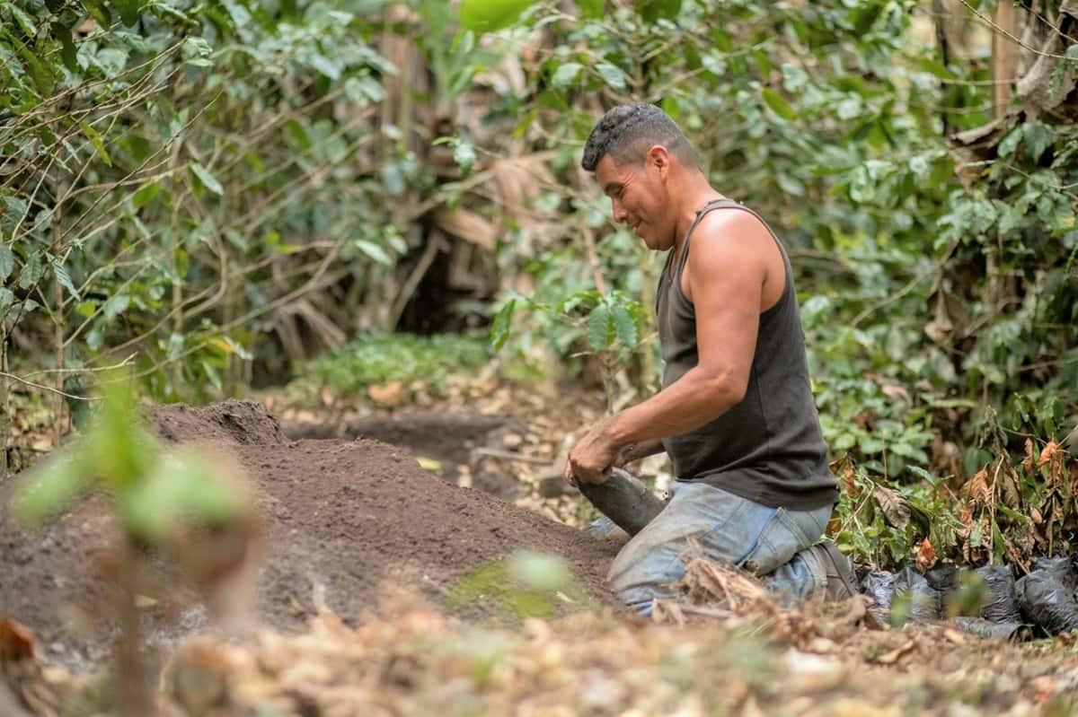 Francisco Polanco kneeling next to a pile of rich compost soil.
