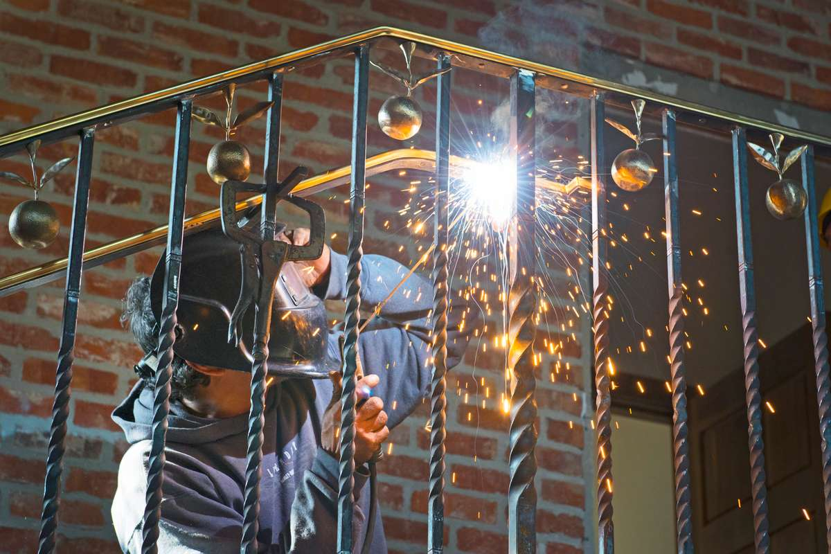 Iron worker in helmet shown welding on Urth Caffe Orange stairway - sparks from weld area