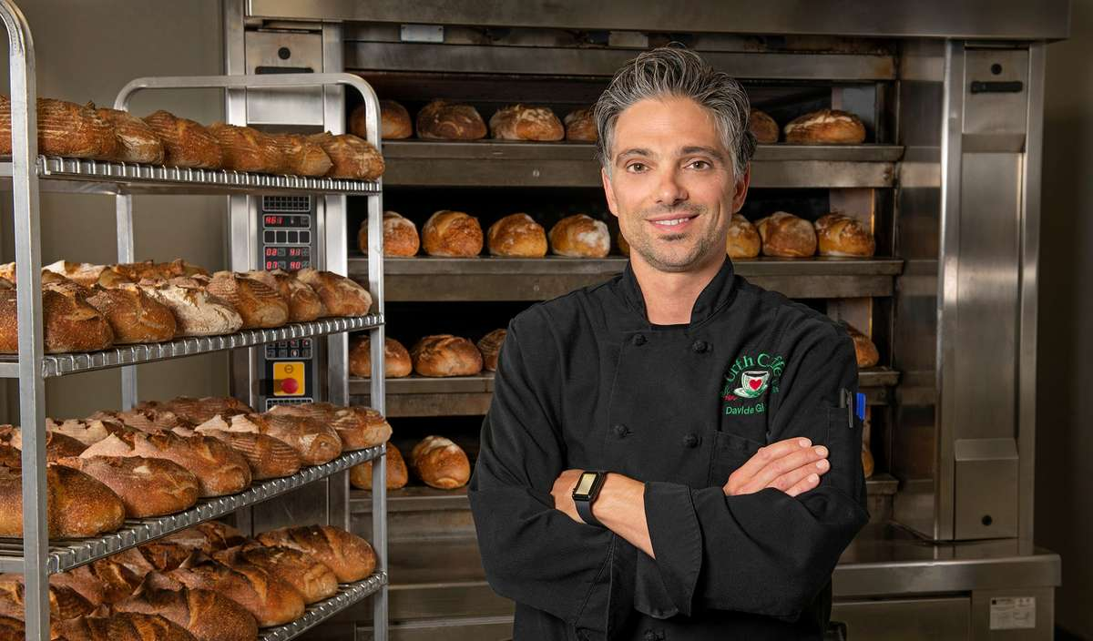 Davide Giova, Urth Caffé Master Baker and Chef, is shown in bakery next to fresh baked breads.