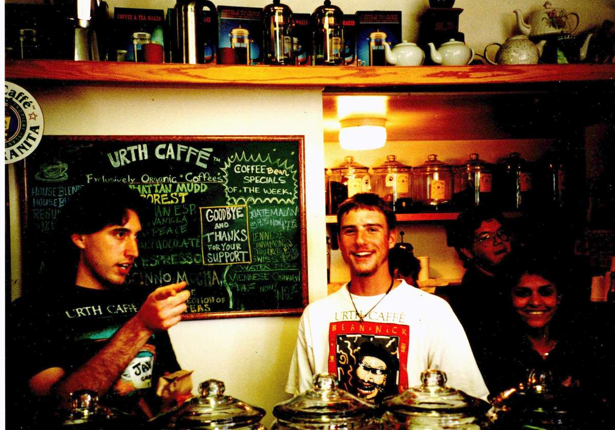 Two men in foreground, woman and man in background of cafe scene