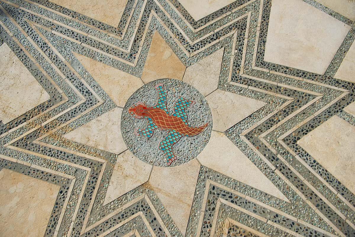 Closeup of tile floor - star shape surrounding circle with gecko design