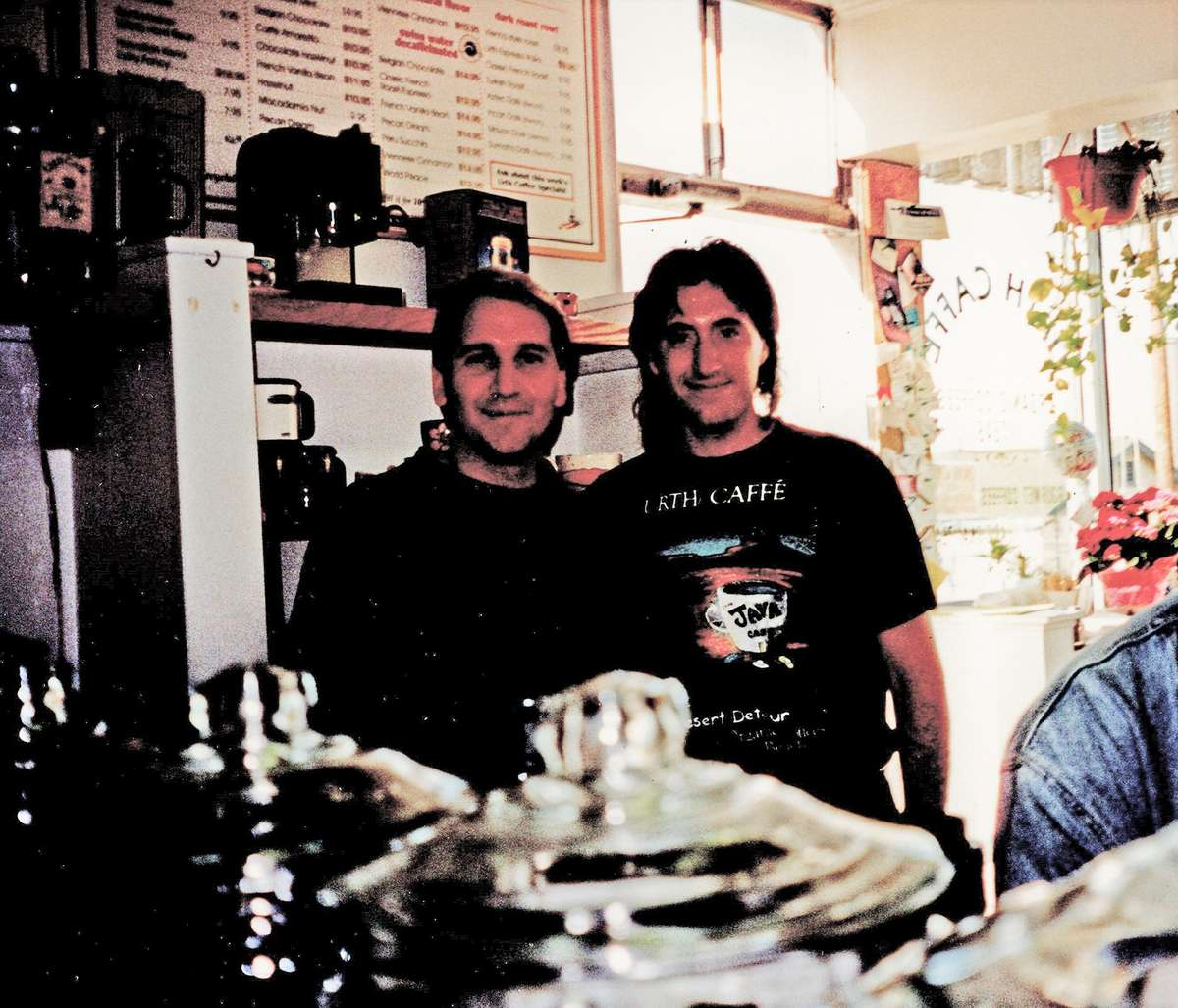 Two men stand in middle of photo inside caffe