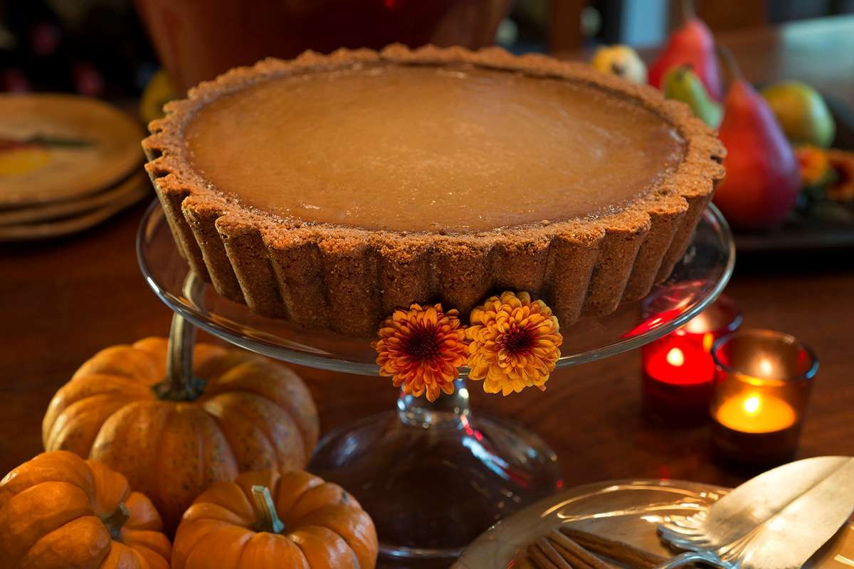Urth Pumpkin Pie displace on elevated cake platter, with mini pumpkins to the left and lighted votive candles on right.